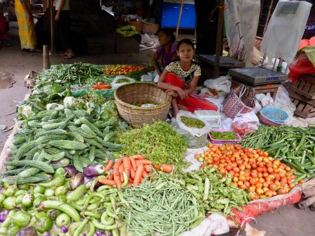market woman sitting, surrounded by fresh vegetables