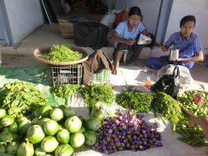 market women eating breakfast among piles of fresh vegetables