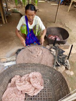 woman cooking rice crackers in hot sand
