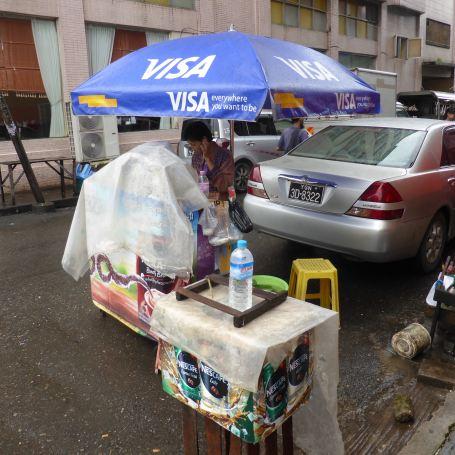 Street vendor under Visa umbrella, on phone