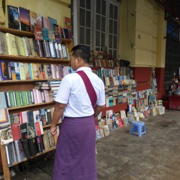 Man looking at books on street