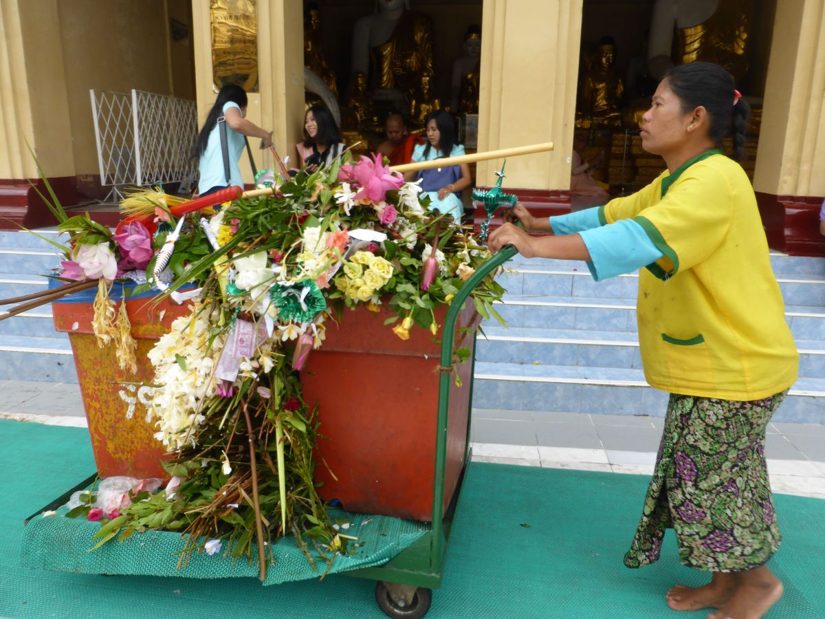 Woman with leftover flowers at pagoda