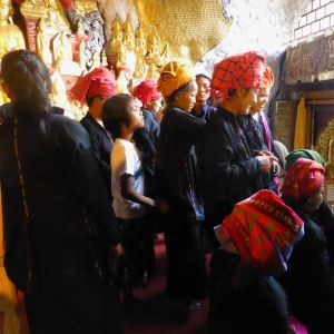 Shan women waiting to put gold leaf on Buddha figures