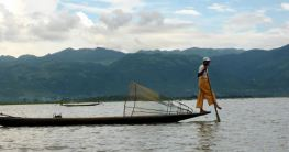 fisherman with foot oar and old-fashioned net