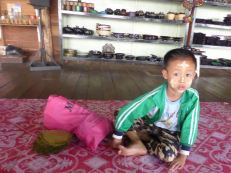 boy waiting for his mom to demo cheroot-making