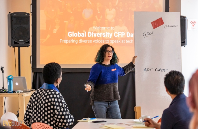 """Kathryn in front of a whiteboard with """"good"""" and """"not great"""". In background """"Welcome to Global Diversity CFP Day"""""""