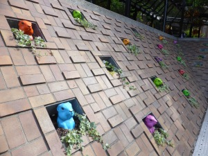 colourful plastic groundhogs poking heads out of brick