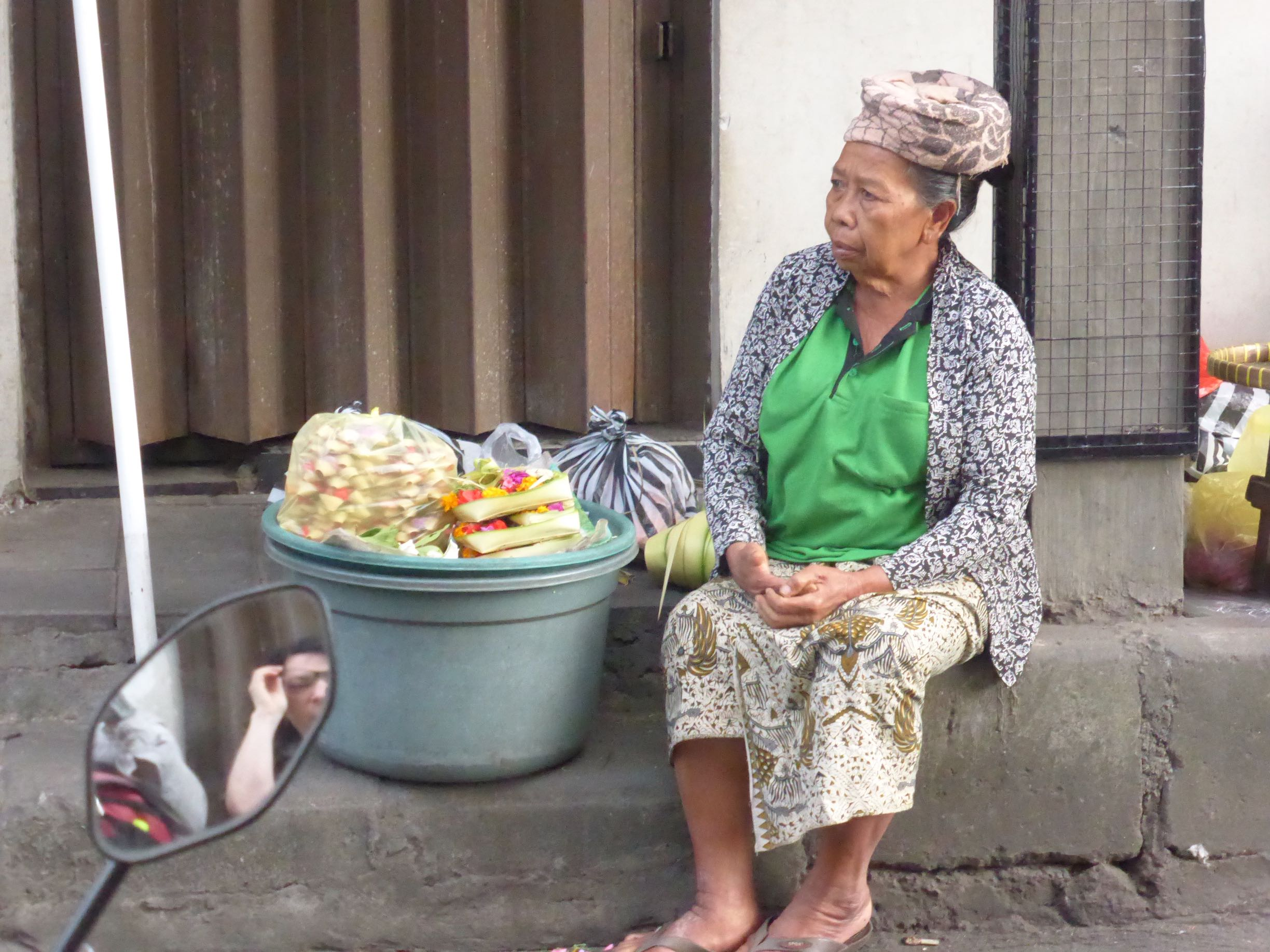 market woman sitting next to bucket with goods