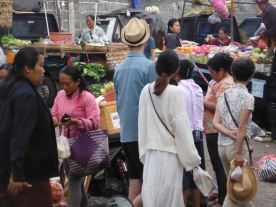 tall man with hat among market shoppers