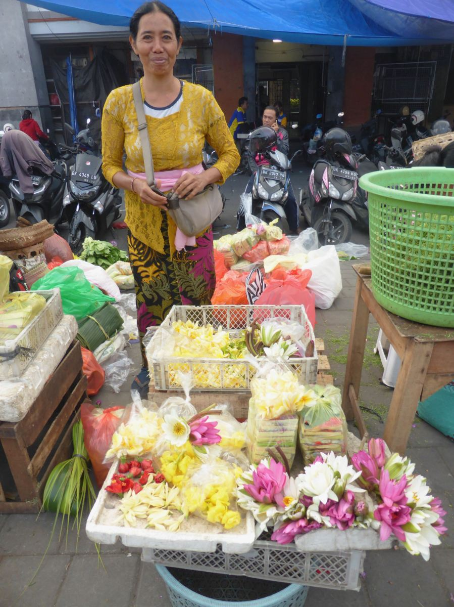 woman smiling in front of flower offerings