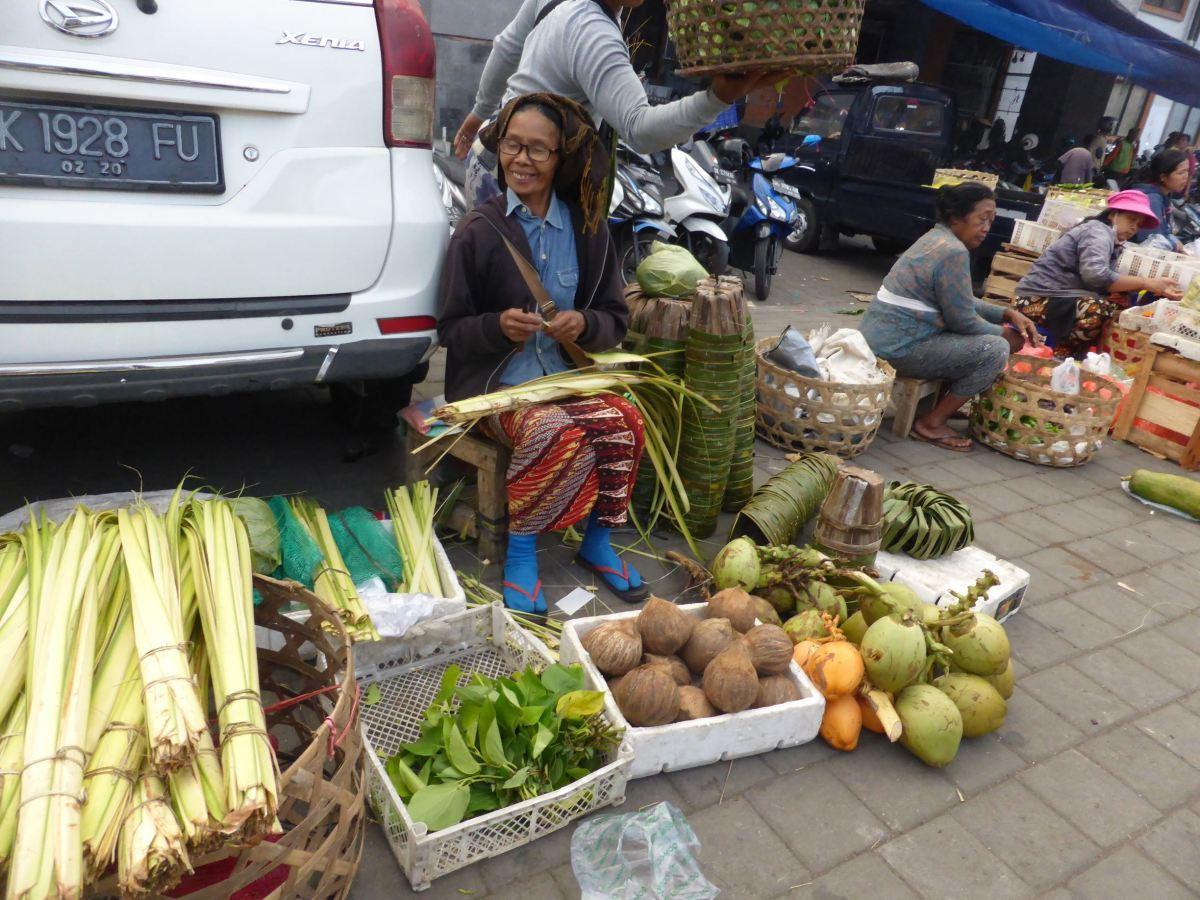 seller sitting behind produce