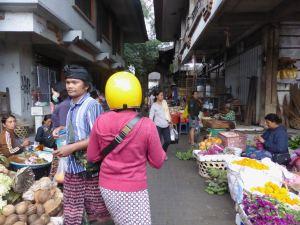 woman in motorcycle helmet walking by man in traditional head covering