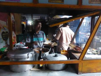 man cooking food at market