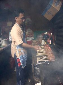 man grilling with smoke